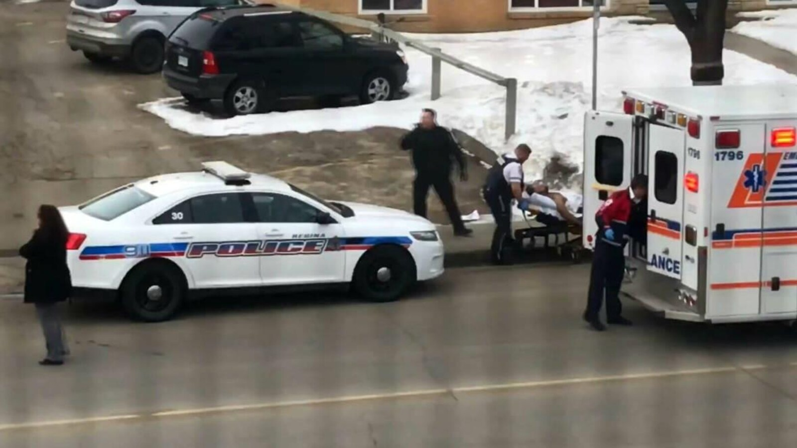Le chauffeur de taxi blessé est allongé sur un brancard. Il s'apprête à être placé dans une ambulance avant son transport à l'hôpital.