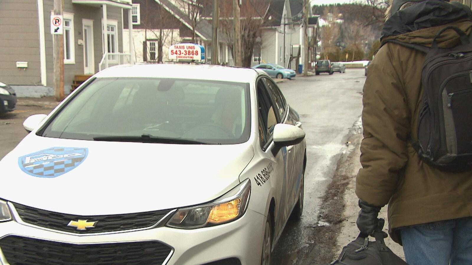 Un homme attend sur le bord de la rue avant de monter dans un taxi.