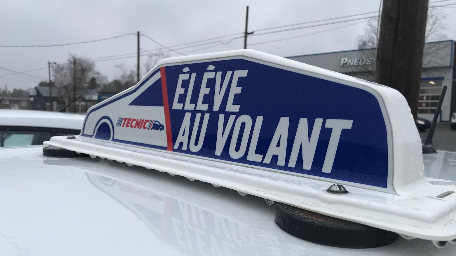 Une affiche sur le toit d'une voiture indique «Élève au volant».