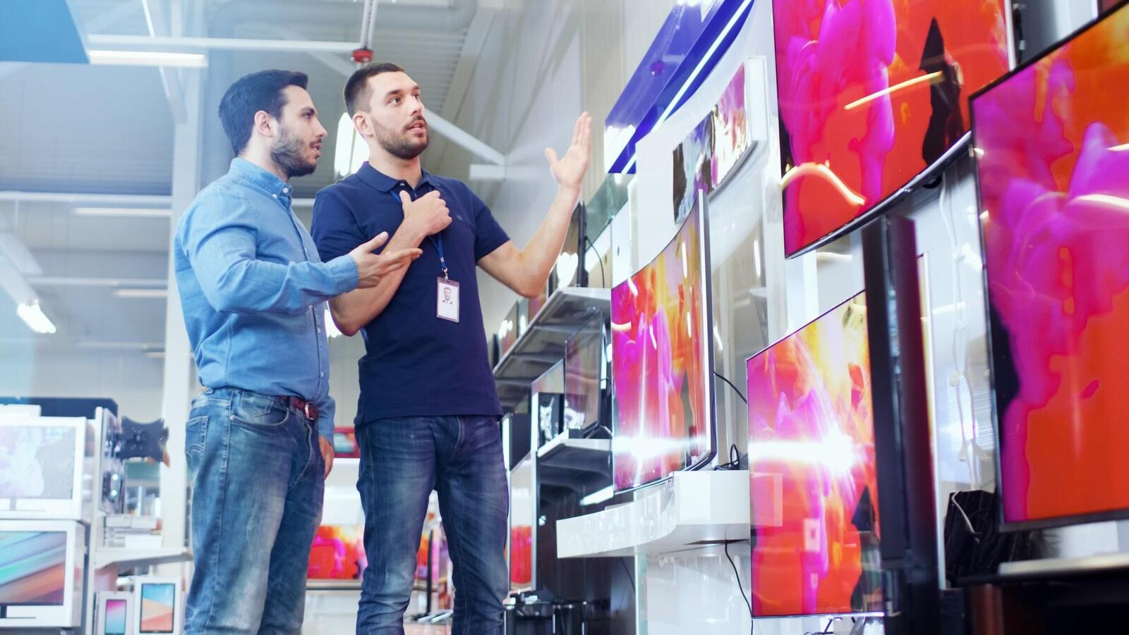 Un vendeur présente des télévisions à un client dans un magasin de produits électroniques.