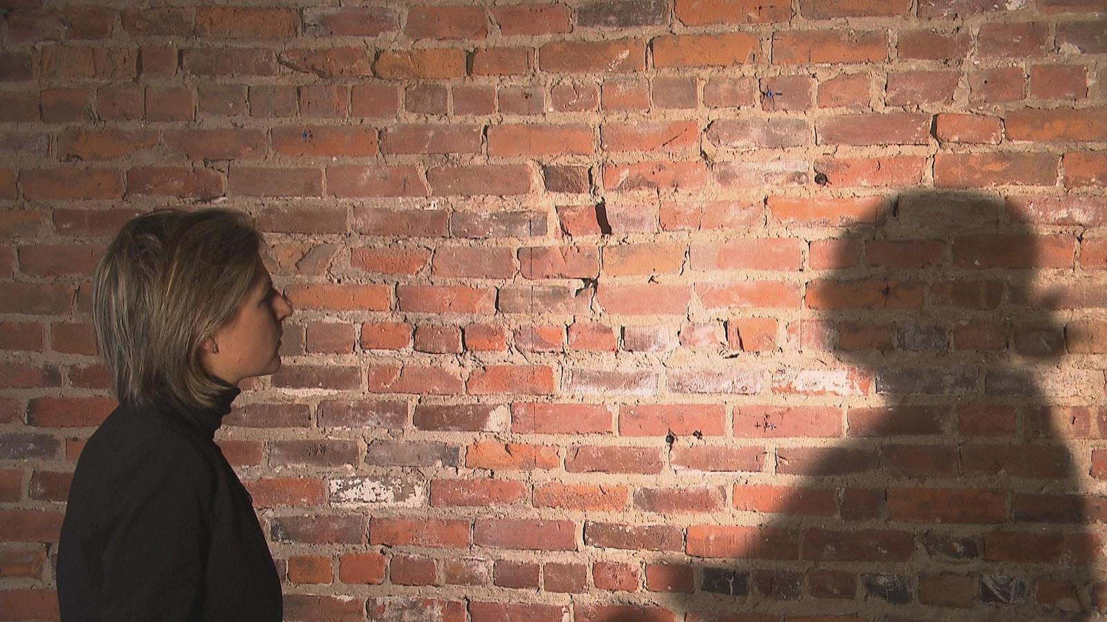 Ombre d'une personne sur un mur de brique en entrevue avec une femme qui porte un chandail noir.