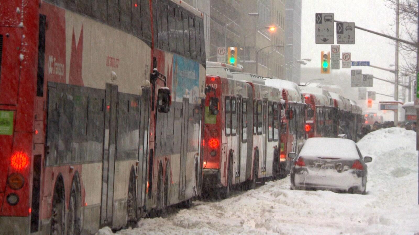 Plusieurs autobus arrêtés à un feu de circulation, sous la neige.