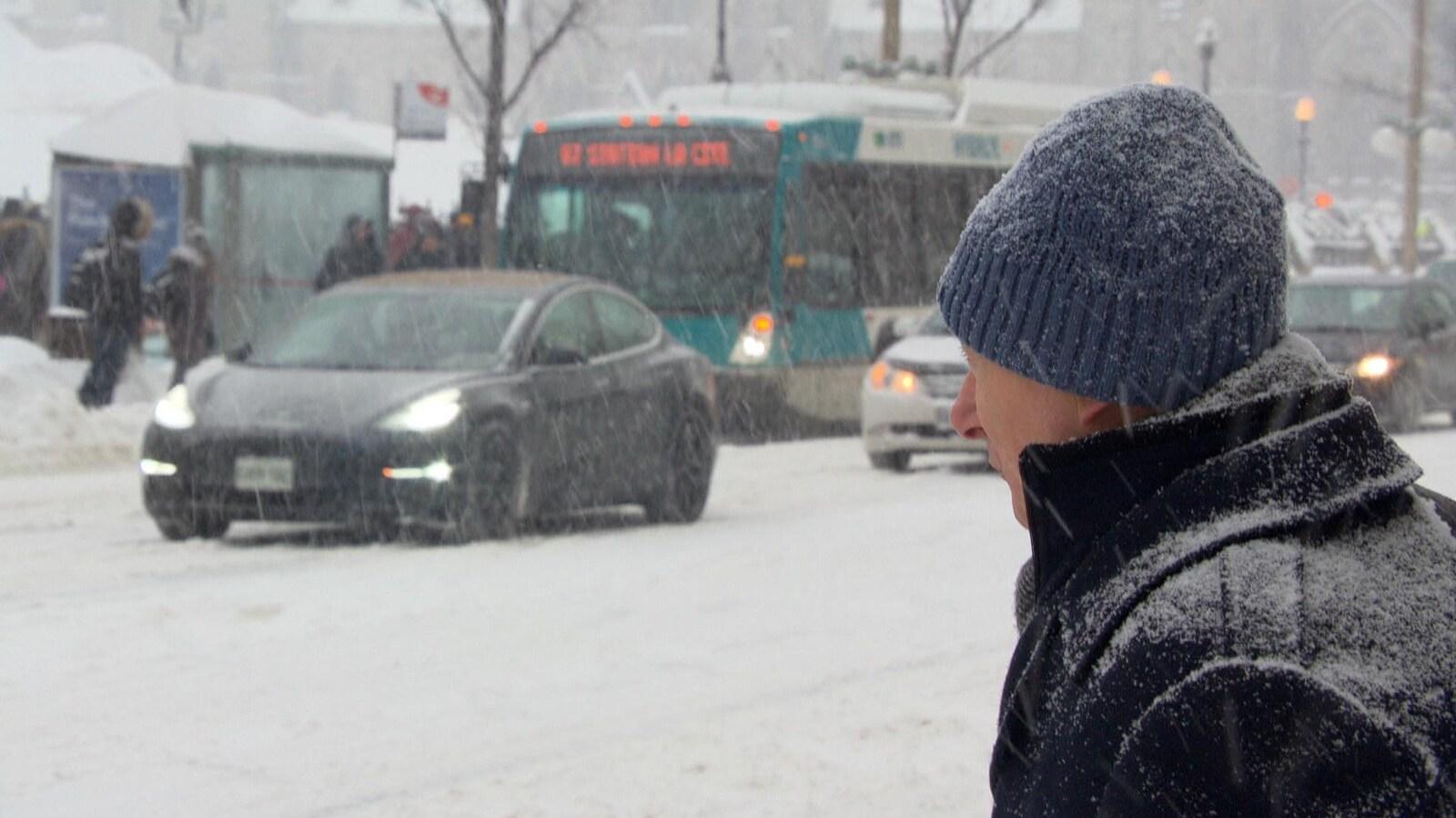 Un homme attend pour traverser la rue sous la neige.