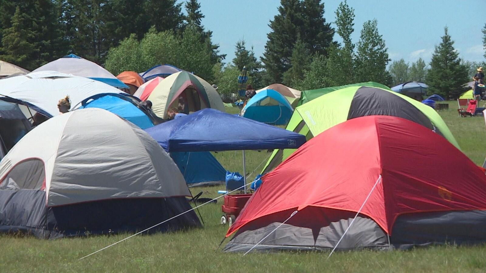 Une quinzaine de tentes très proches les unes des autres, dans un champ.