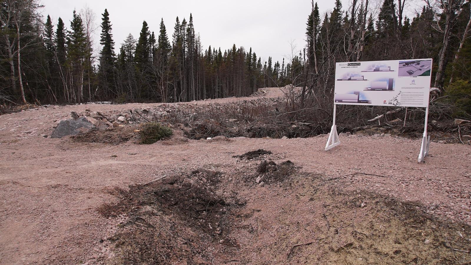 Une affiche du projet Mason Graphite devant un terrain vague