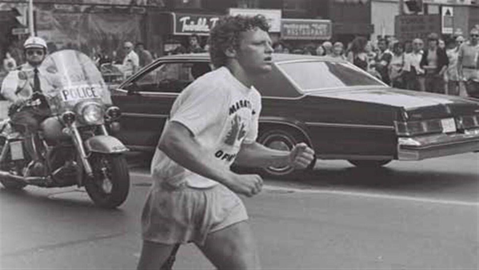 Un coureur avec une jambe artificielle court dans une rue alors qu'il est escorté des policiers. La photo est en blanc et noir et date des années 1980.
