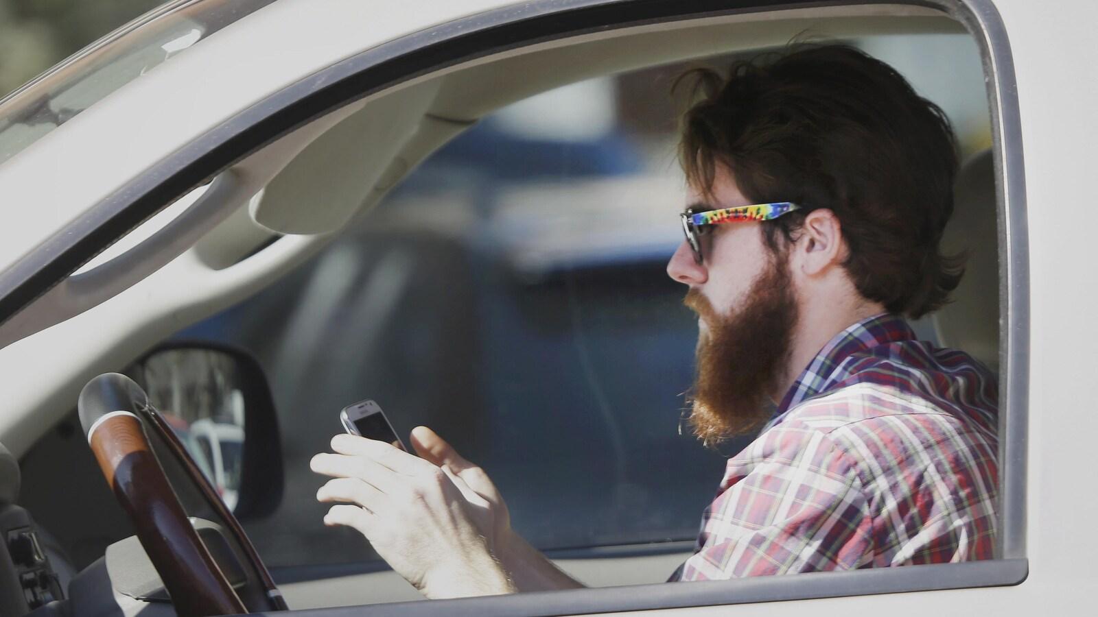 Un automobiliste texte au volant.