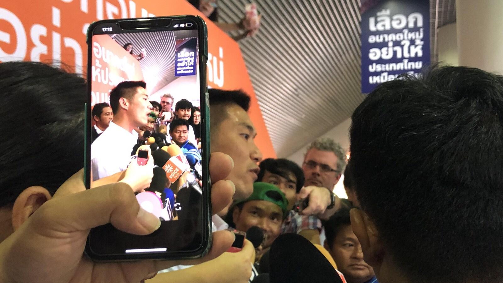 Une personne prend une photo d'un homme politique à l'aide d'un téléphone intelligent.
