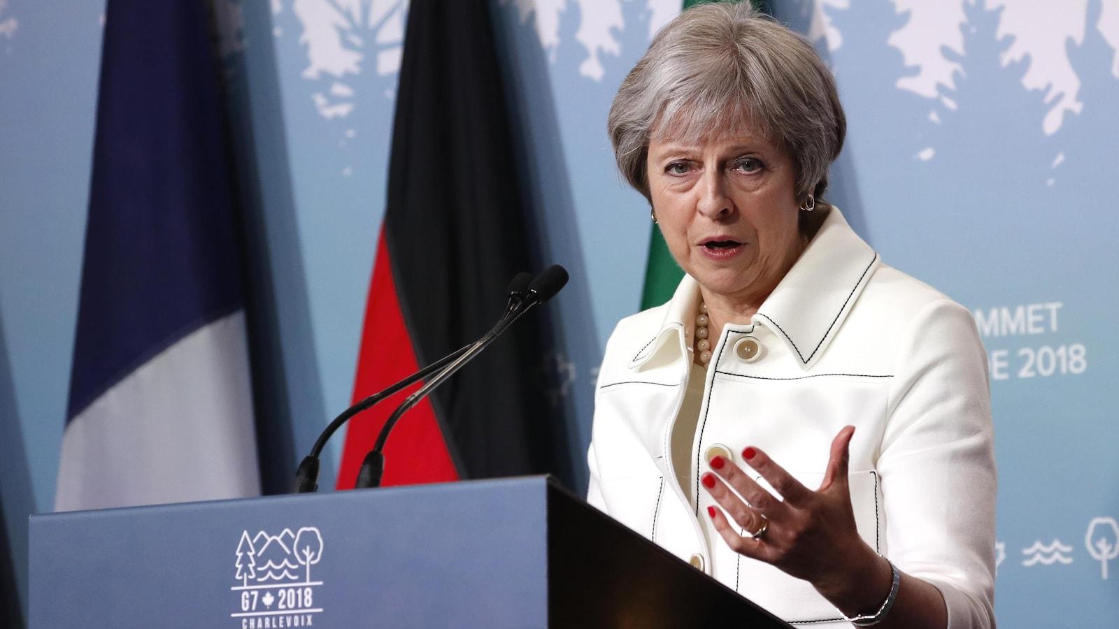 La première ministre britannique Theresa May lors du Sommet du G7 tenu à La Malbaie prend la parole derrière une tribune.