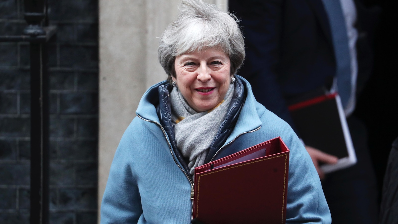 Une femme porte un manteau et tient dans une de ses mains un cartable.
