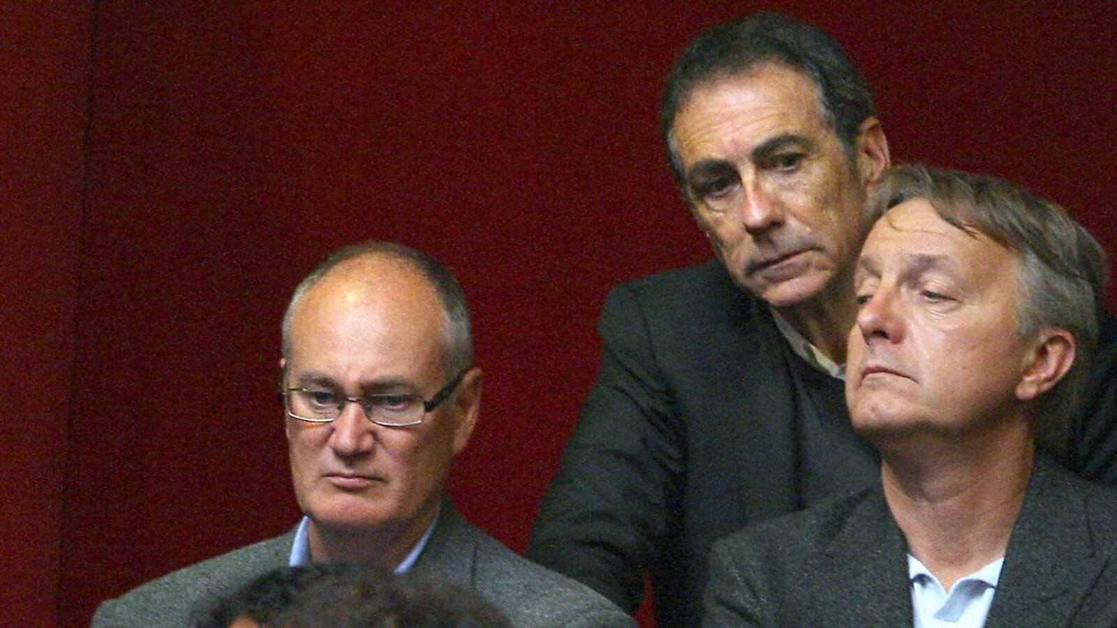 Trois hommes semblent regarder différentes choses.
