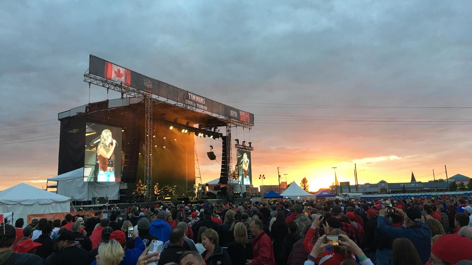 Une foule compacte devant une scène assiste à un spectacle sur fond de coucher de soleil.
