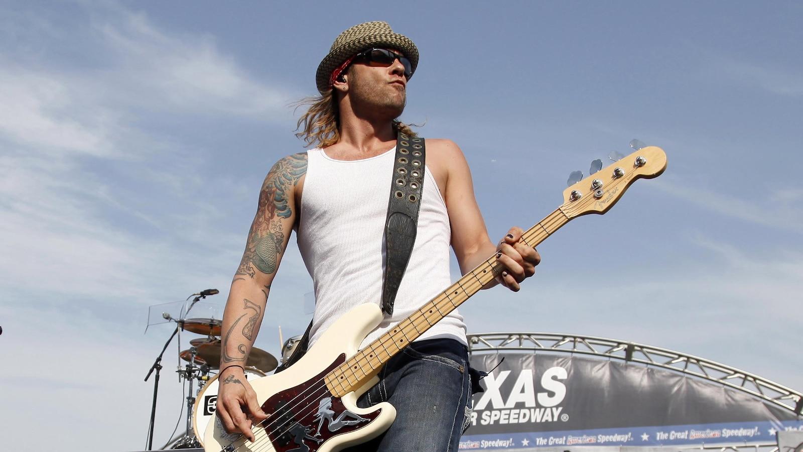 Todd Harrell joue de la guitare basse sur une scène extérieure.