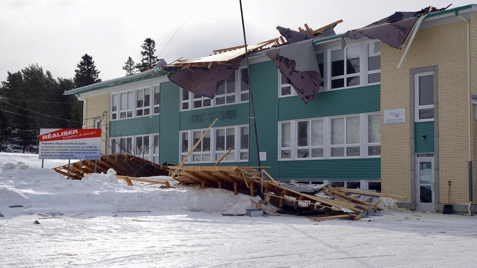Plusieurs poutres et planches de bois jonchent le sol devant une école de deux étages.