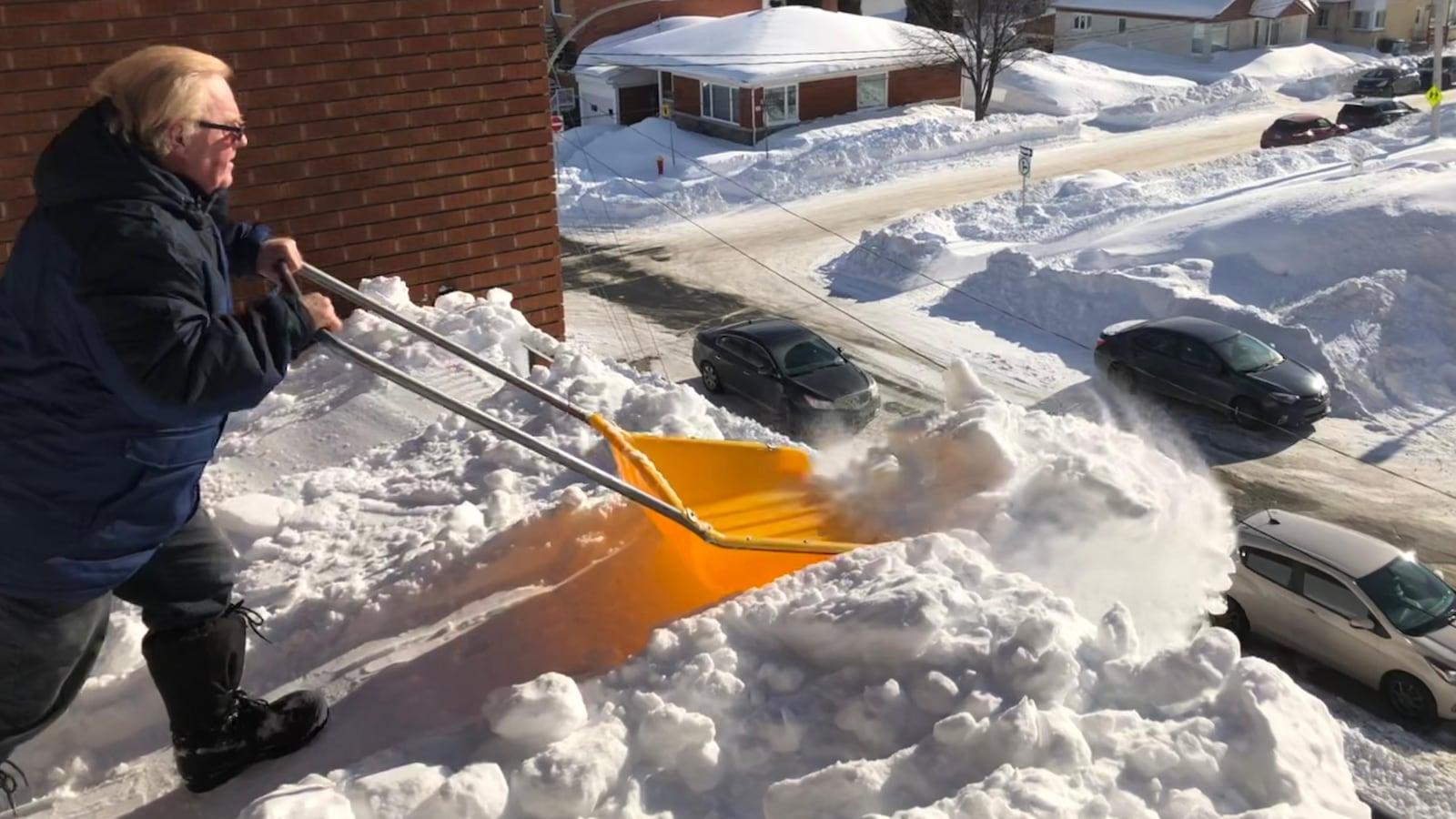 Un homme pousse la neige du toit vers le sol.