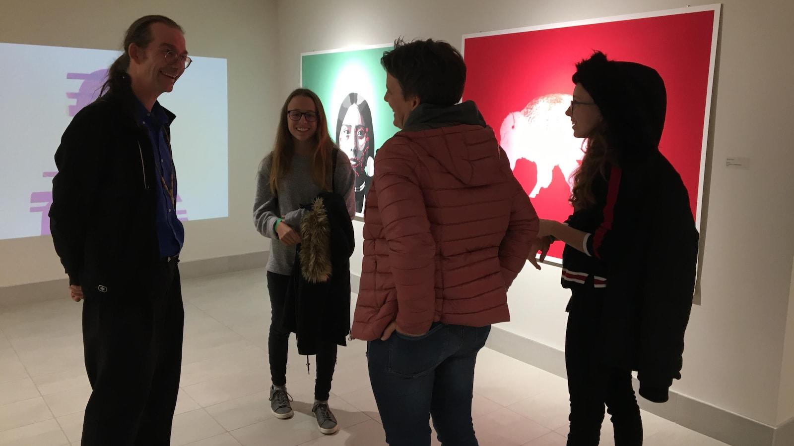 Trois touristes dans un musée discutent avec le guide.