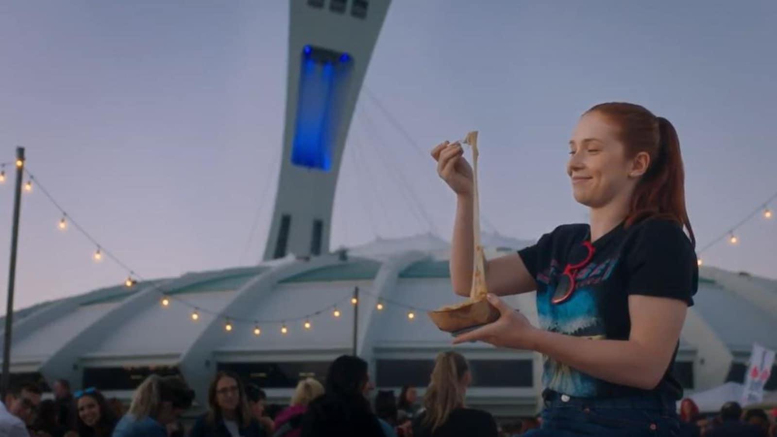 Une jeune femme mange une poutine devant le stade olympique.
