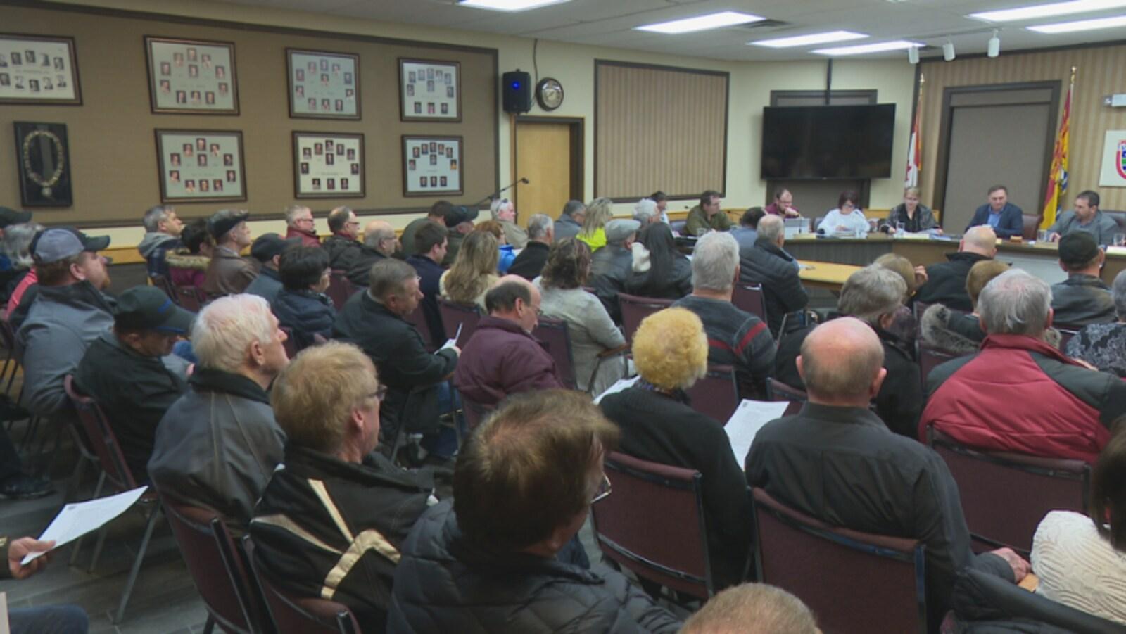 Des dizaines de citoyens assis dans la salle écoutent les conseillers débattre des affaires municipales.