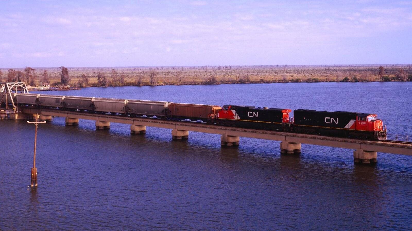 Les modifications à la Loi sur les transports au Canada permettront aux producteurs de grain d'avoir un droit d'arbitrage envers les transporteurs ferroviaires en cas de retards de livraison. Un train du Canadien National qui traverse un pont au-dessus de l'eau.