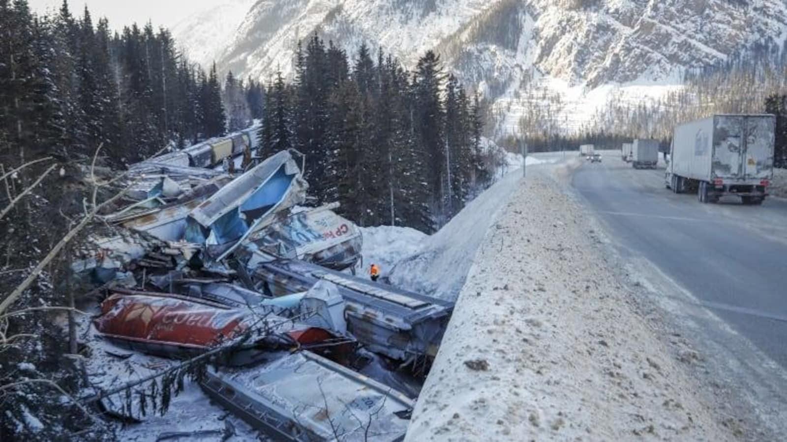 Une dizaine de wagons brisés sont empilés sur le bord d'une route enneigée.