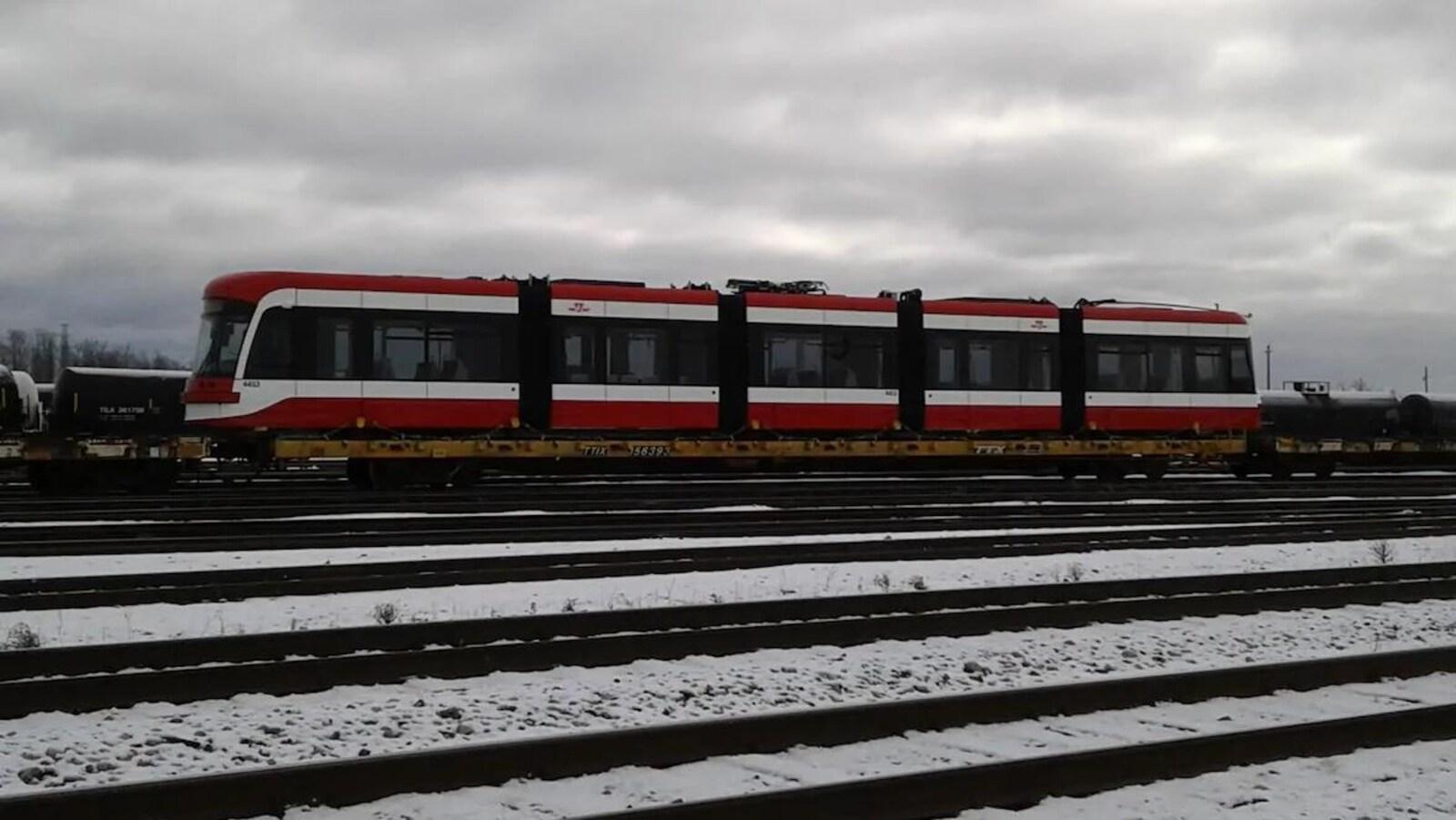 Un tramway chargé sur un train dans une gare de triage.