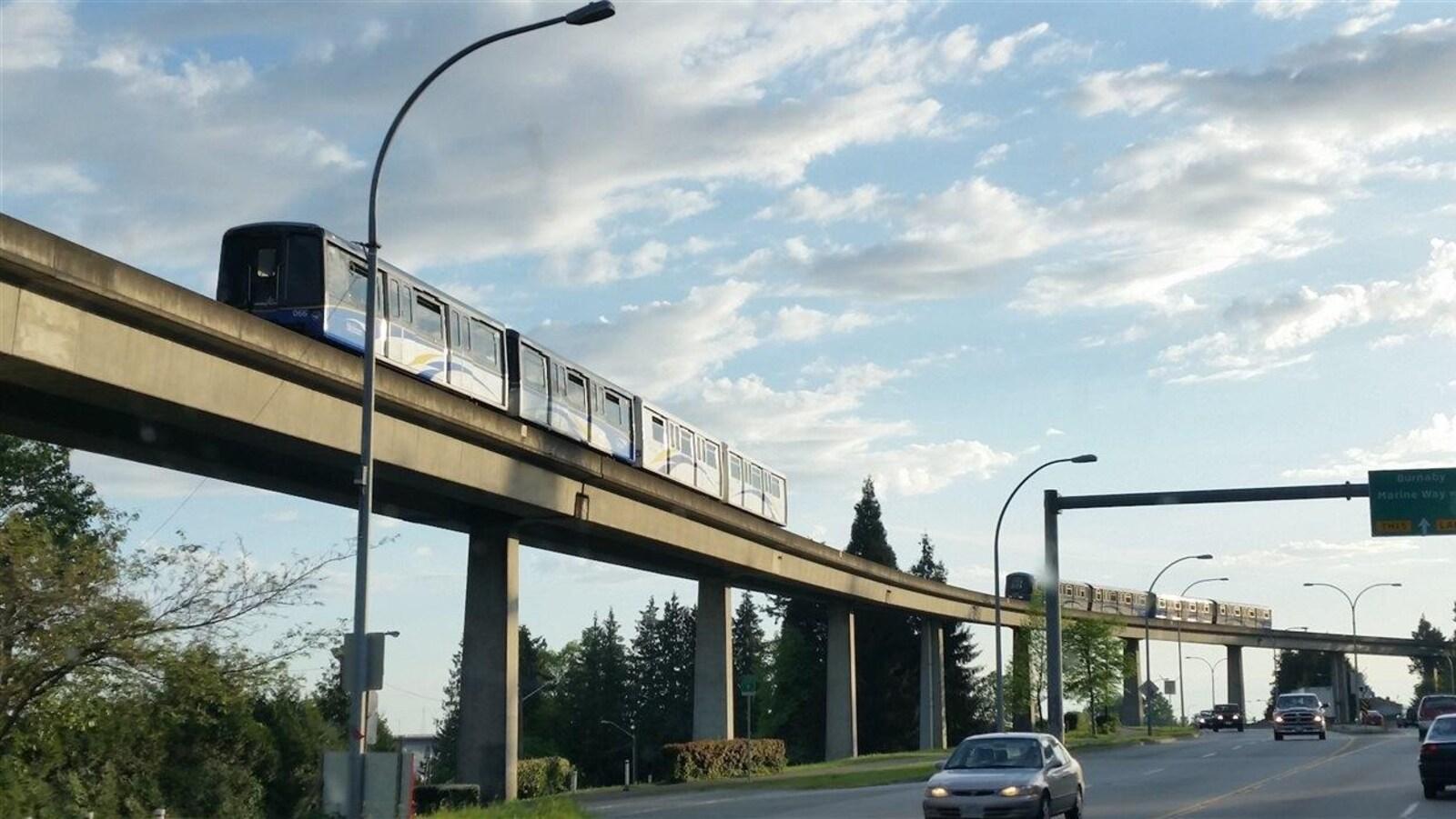 Deux trains du réseau de Skytrain de TransLink circulent au-dessus d'une rue sur laquelle passent des voitures.