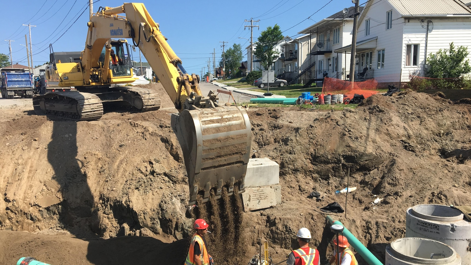 Des travailleurs dans une fosse creusée par une pelle mécanique.
