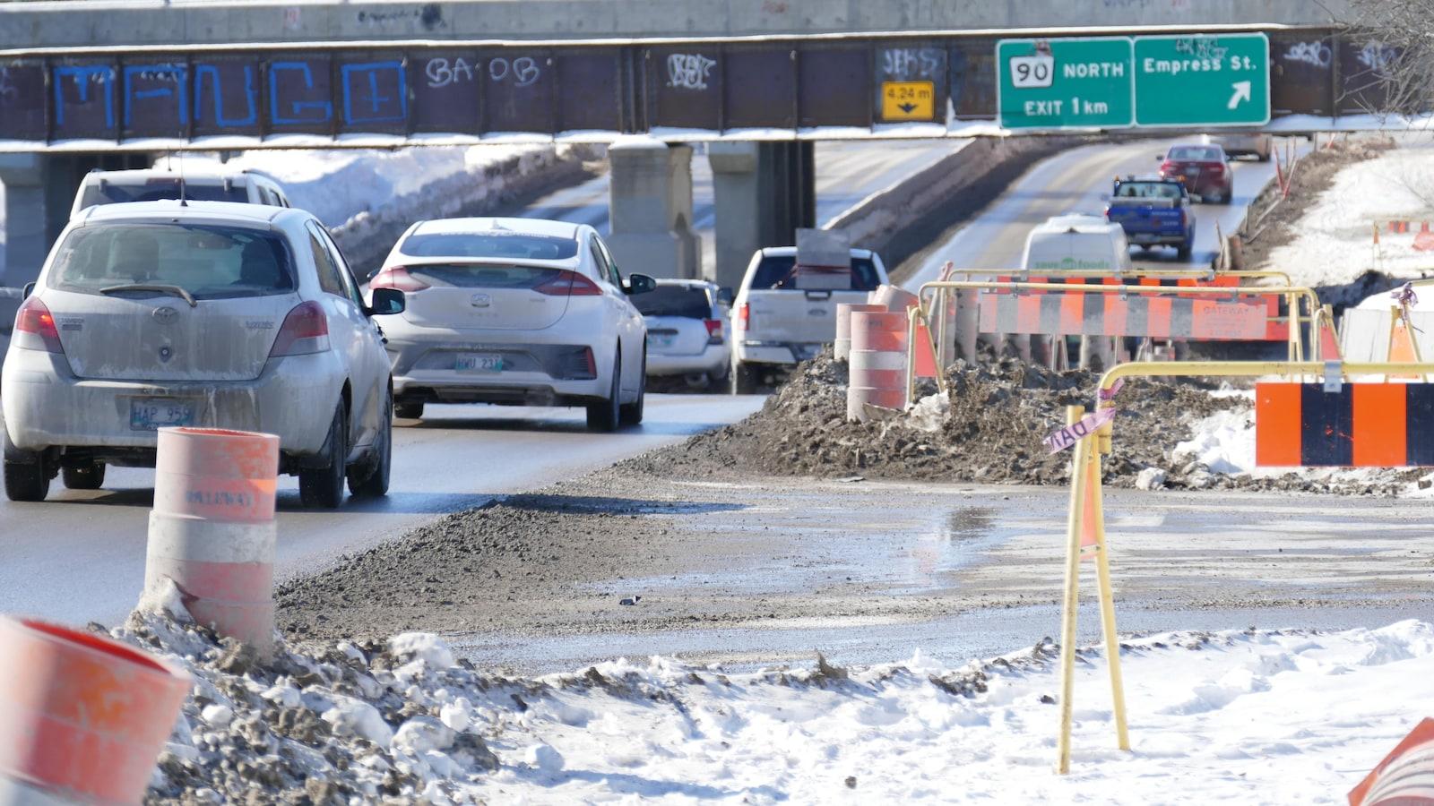 Des voitures circulent en hiver sur une route où il y a des travaux.