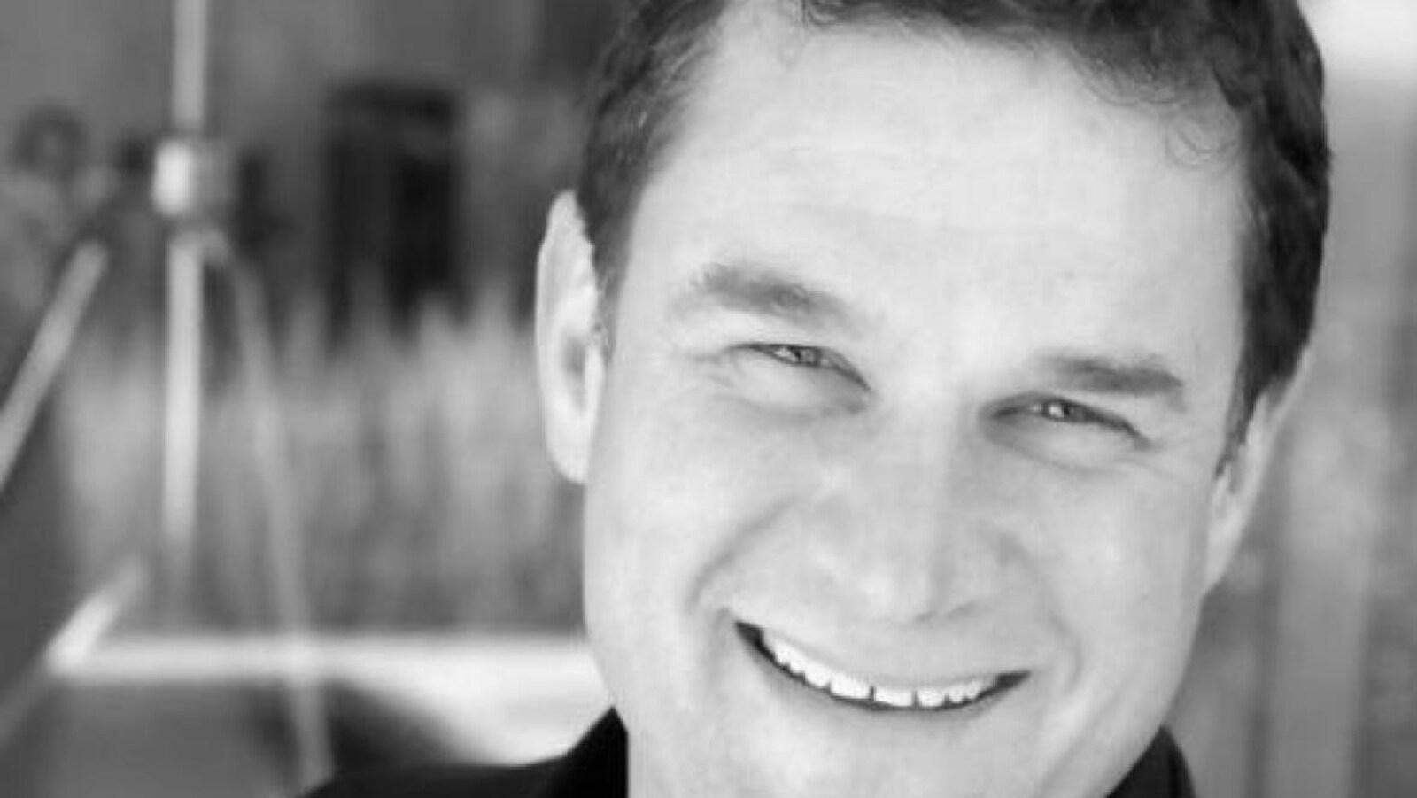 Un homme sourit dans une photo en noir et blanc.