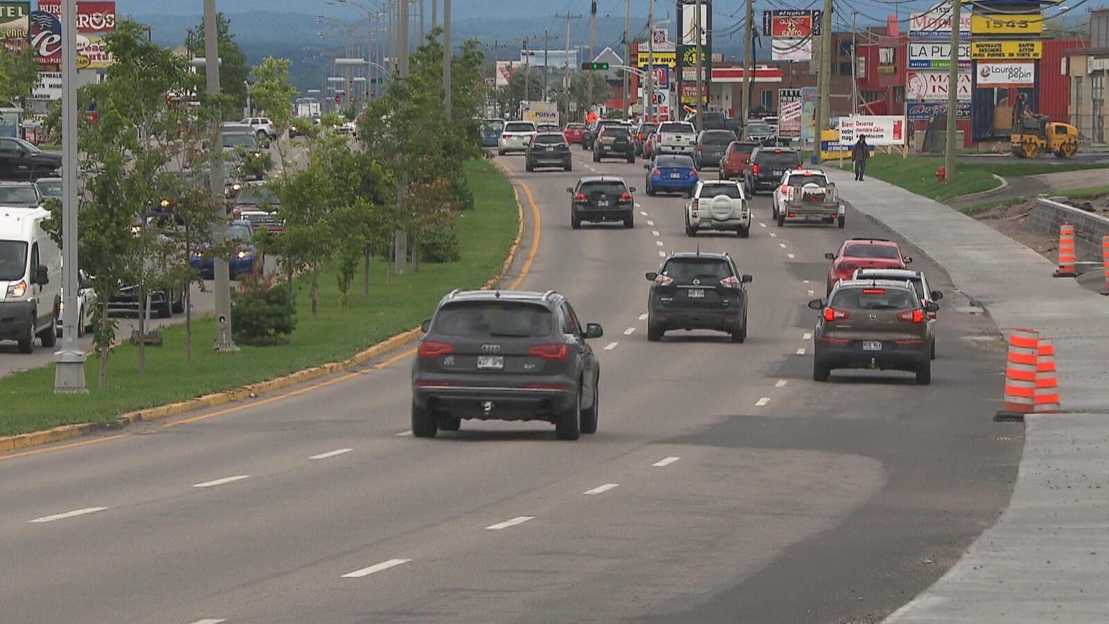 Des voitures circulent sur les trois voies du boulevard Talbot alors qu'un piéton marche sur le trottoir.