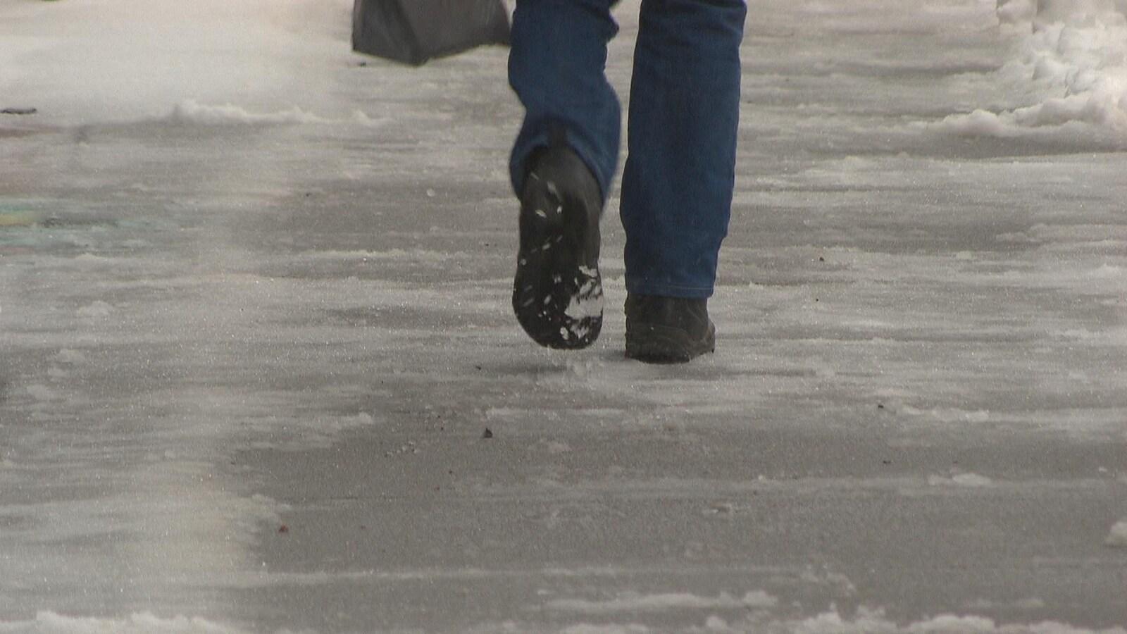 Pieds d'une personne qui marche sur un trottoir glacé