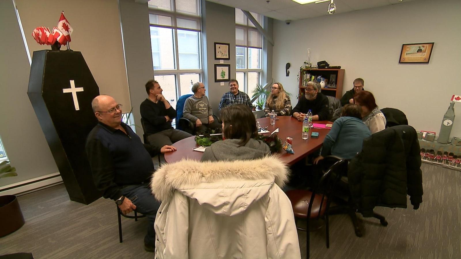 Une douzaine de personnes dans le bureau du ministre du Développement social, Jean-Yves Duclos, à Québec.