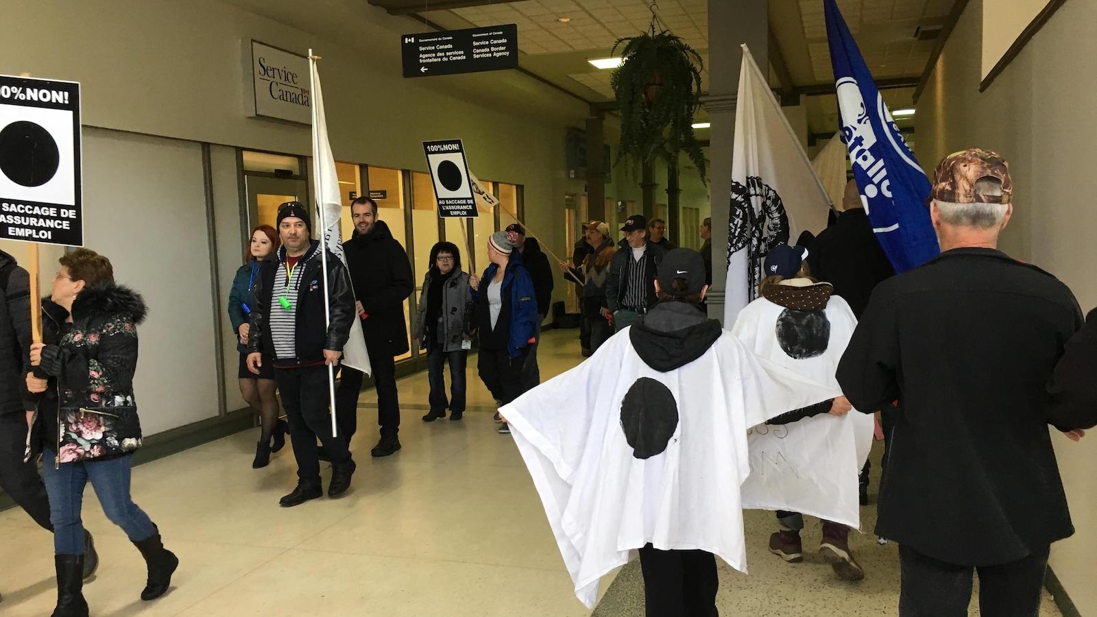 Des manifestants devant les bureaux de Services Canada à Baie-Comeau dans un centre commercial