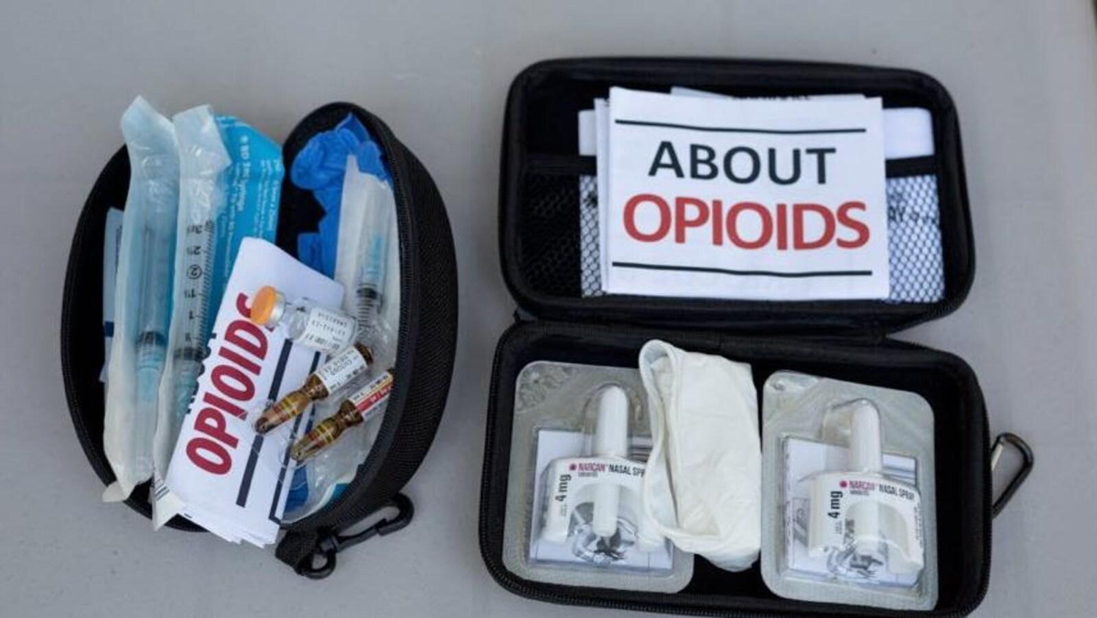 Deux pochettes noires contiennent des seringues et de la drogue.