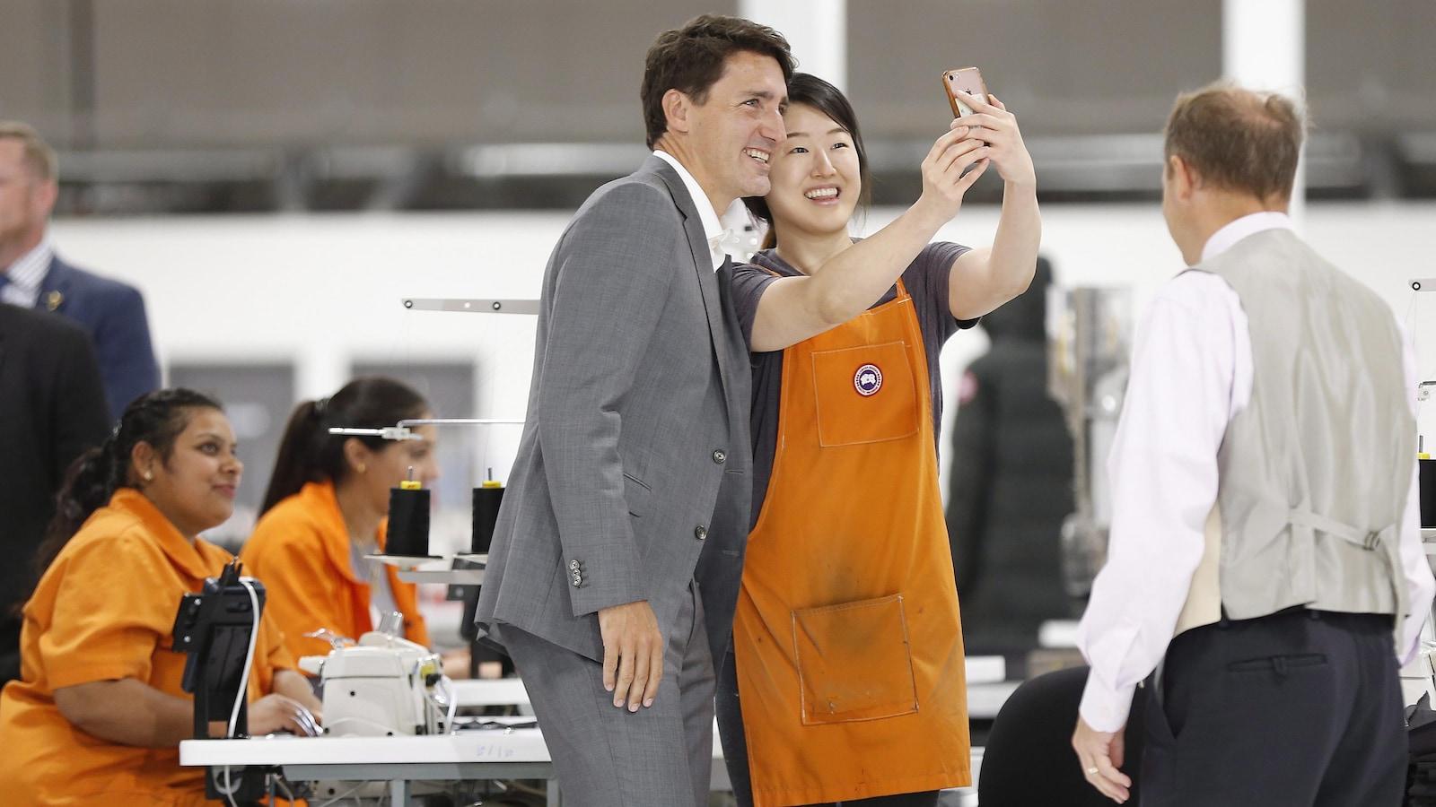 Justin Trudeau avec une travailleuse qui prend un autoportrait.