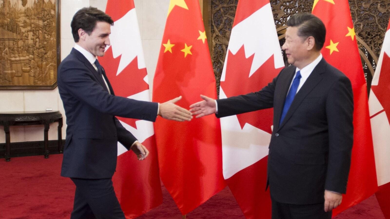 Justin Trudeau et le président chinois Xi Jinping, devant des drapeaux de la Chine et du Canada, sur le point de se serrer la main.
