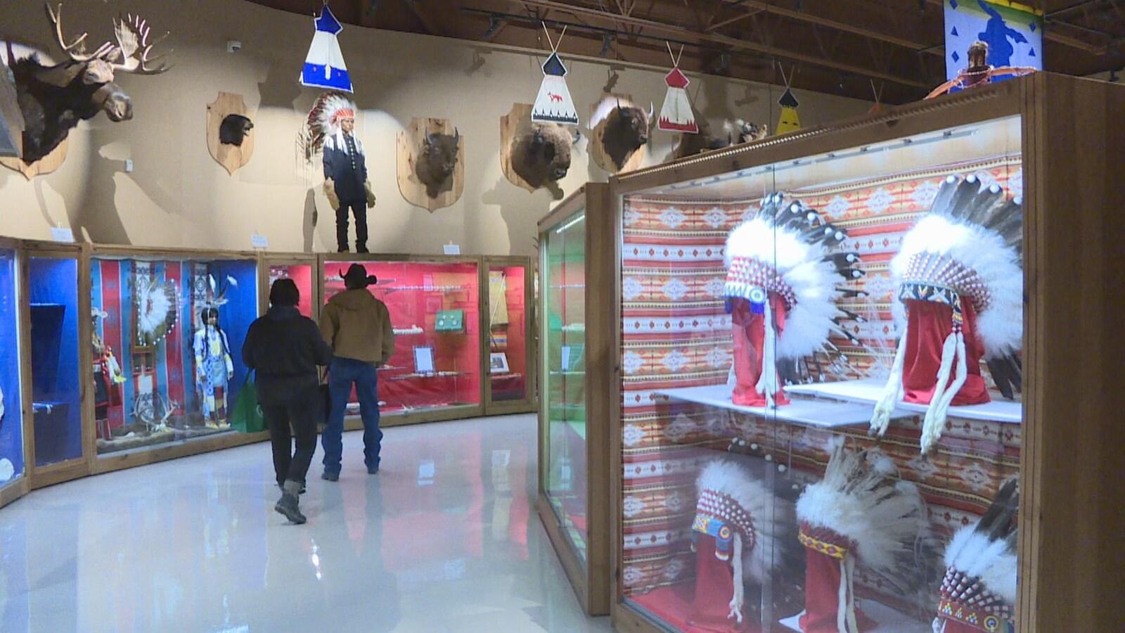 Deux hommes de dos explorent le musée. À droite, il y a des coiffures traditionnelles autochtones derrière des vitrines, à gauche, des vêtements traditionnels.