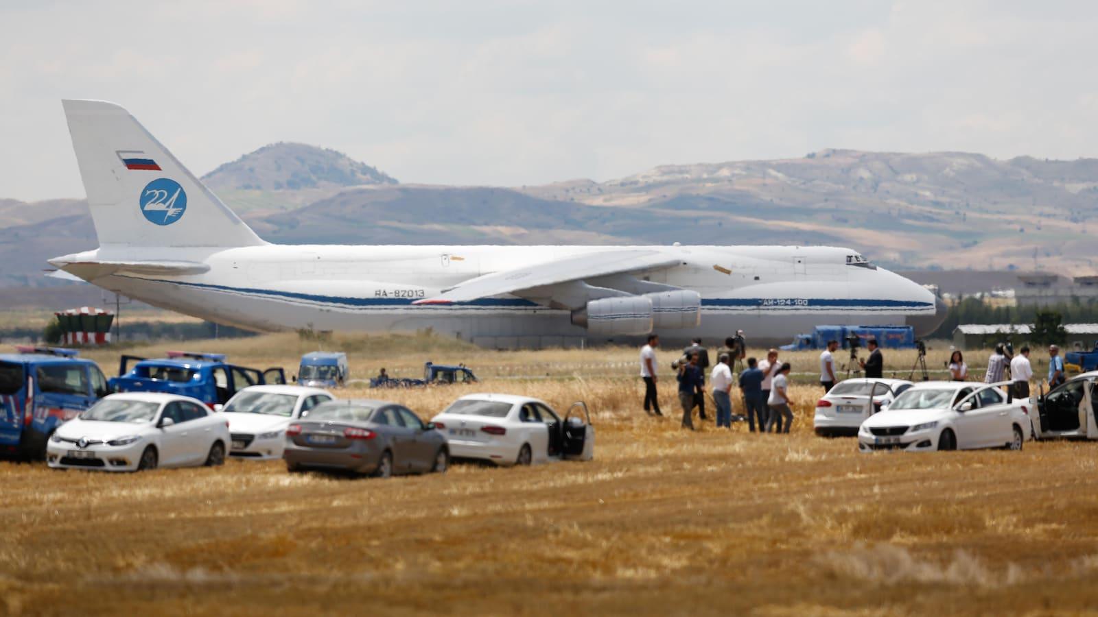Un Antonov 124 de l'armée russe est visible derrière plusieurs véhicules. Des journalistes sont présents.