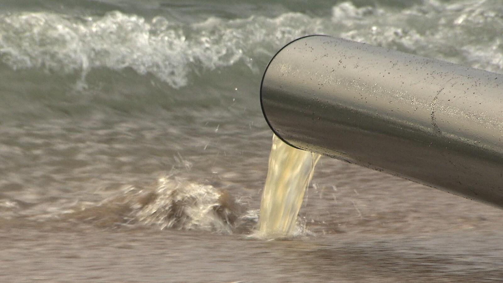 Un tuyau déverse de l'eau brunâtre dans le fleuve Saint-Laurent.