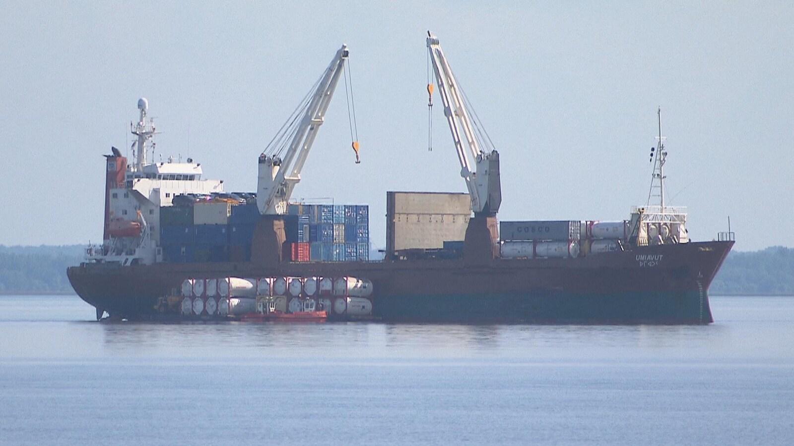 Des grues s'activent sur le cargo pour le décharger de sa cargaison.