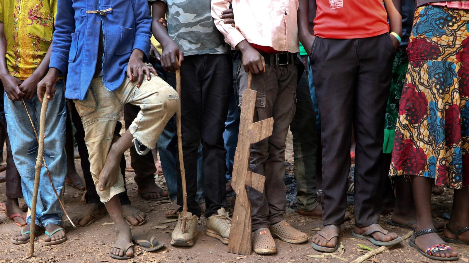 Vue d'une douzaine d'enfants alignés dehors dont on ne voit que les jambes et les pieds.