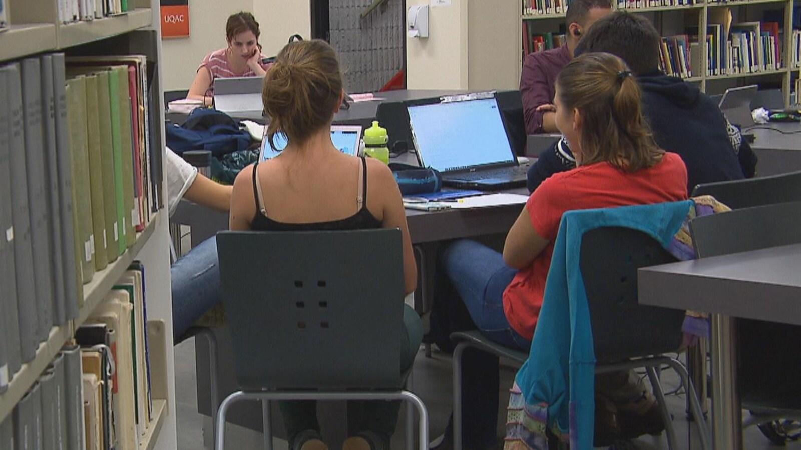 On voit des étudiants qui travaillent autour d'une table à la bibliothèque.
