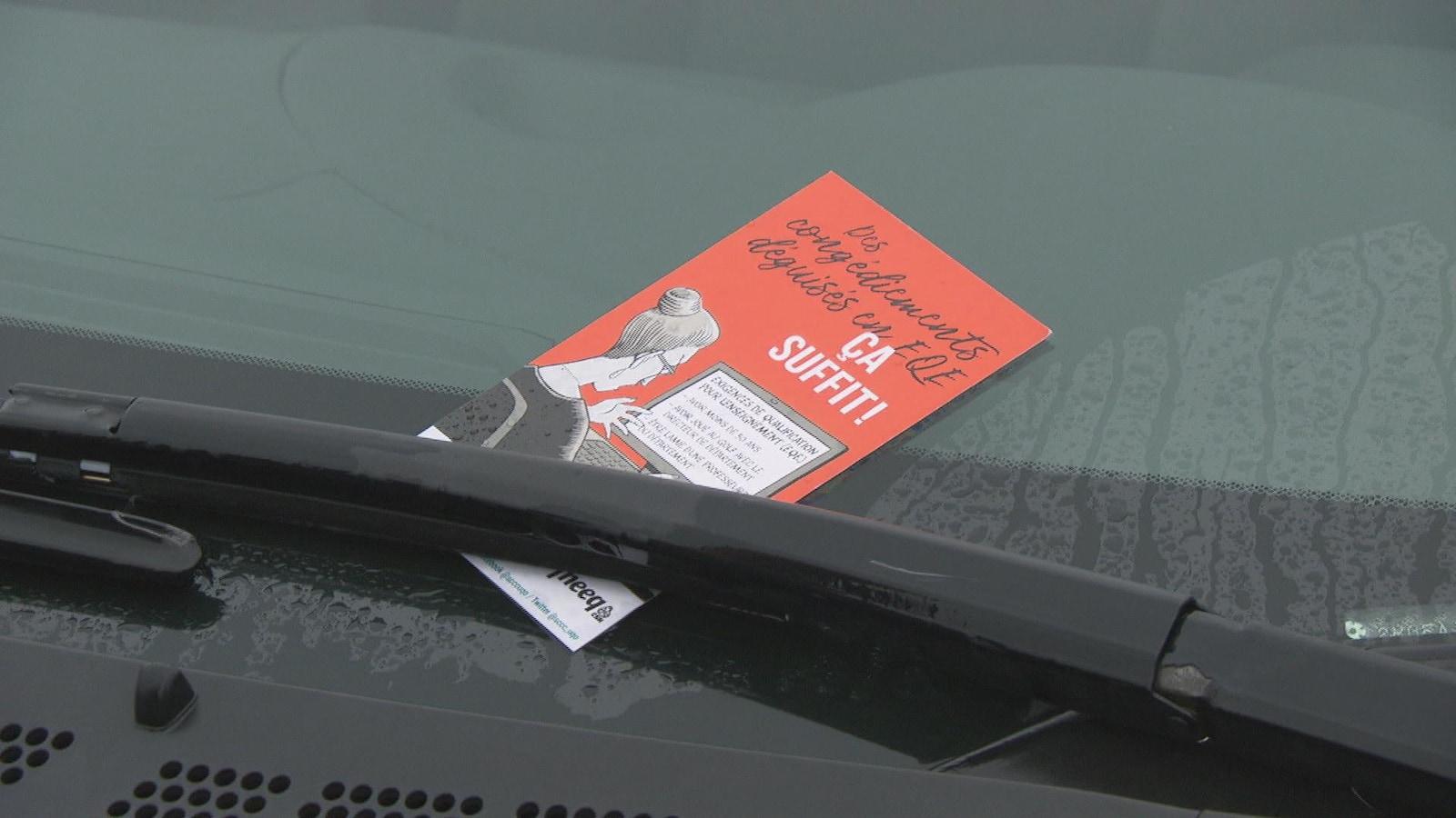 Un tract rouge sur le pare-brise d'une voiture.