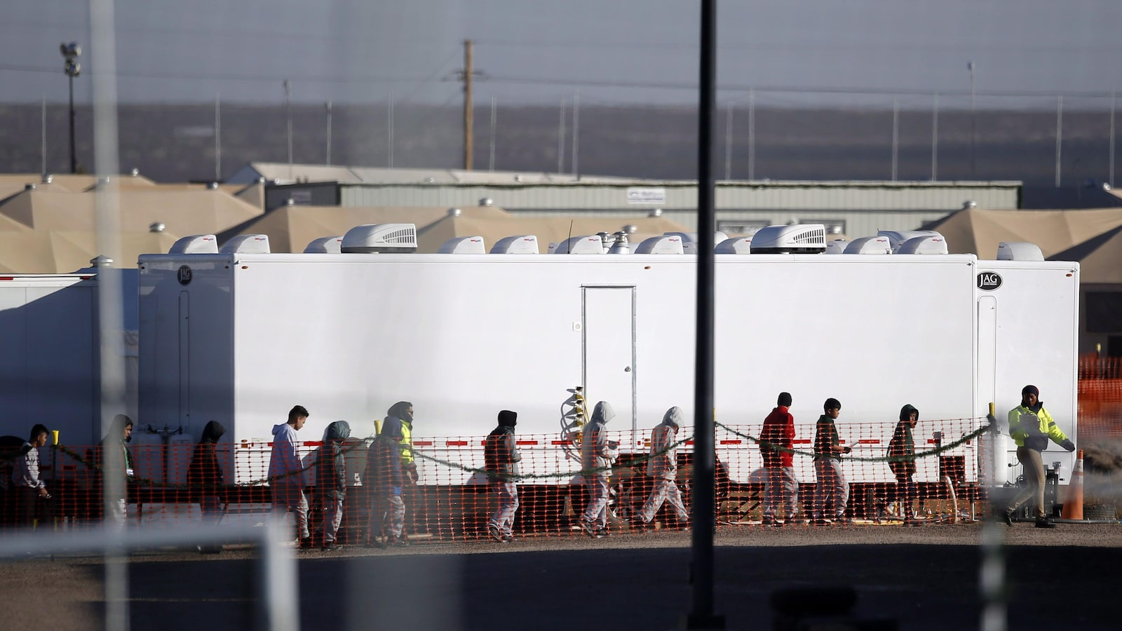 Des adolescents migrants marchent en file dans le camp de Tornillo au Texas.