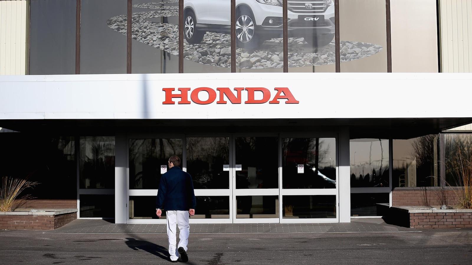 Un employé entre dans une usine de Honda.