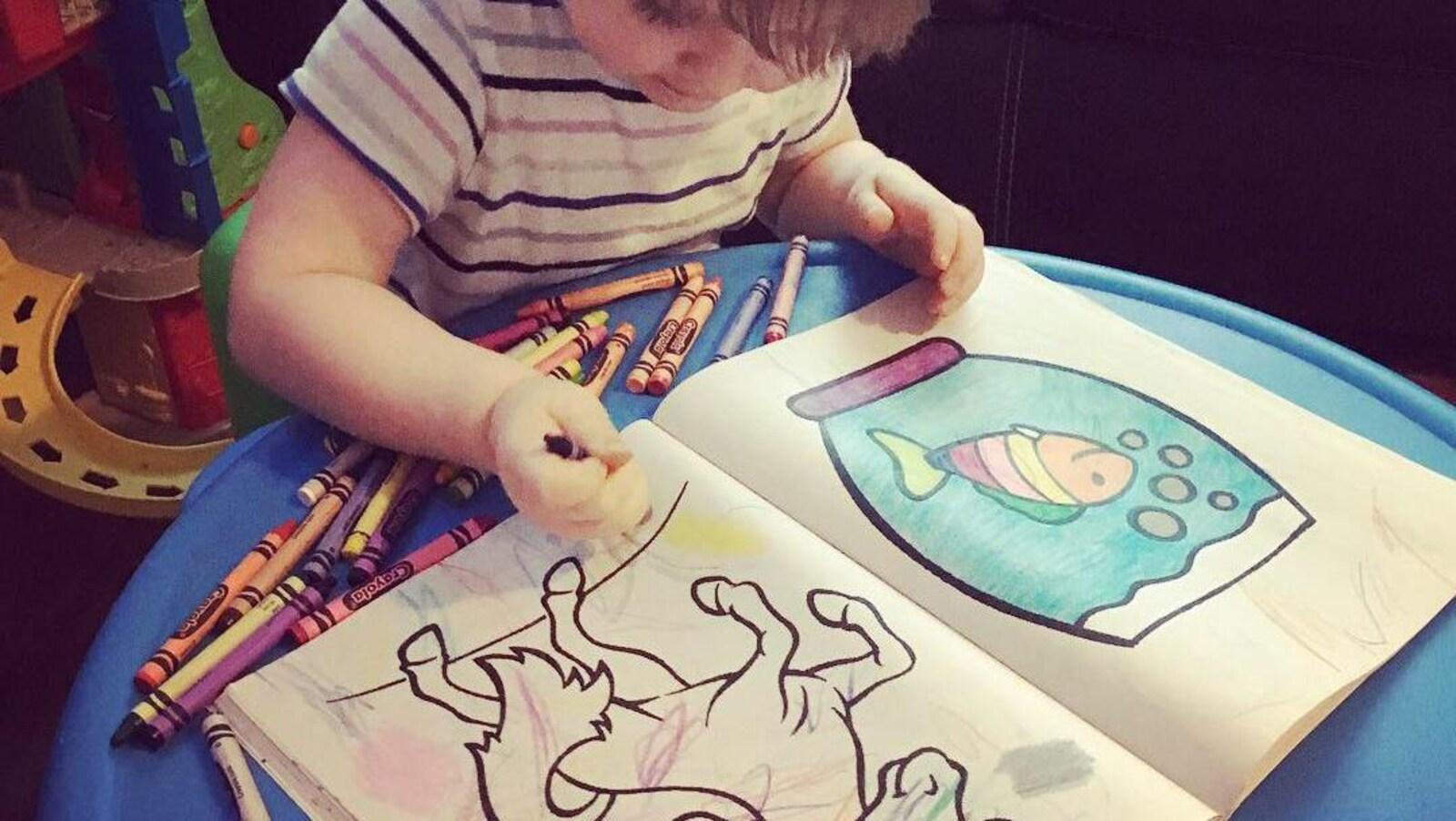 Une petite fille en train de colorier un dessin de cheval avec des crayons de cire.