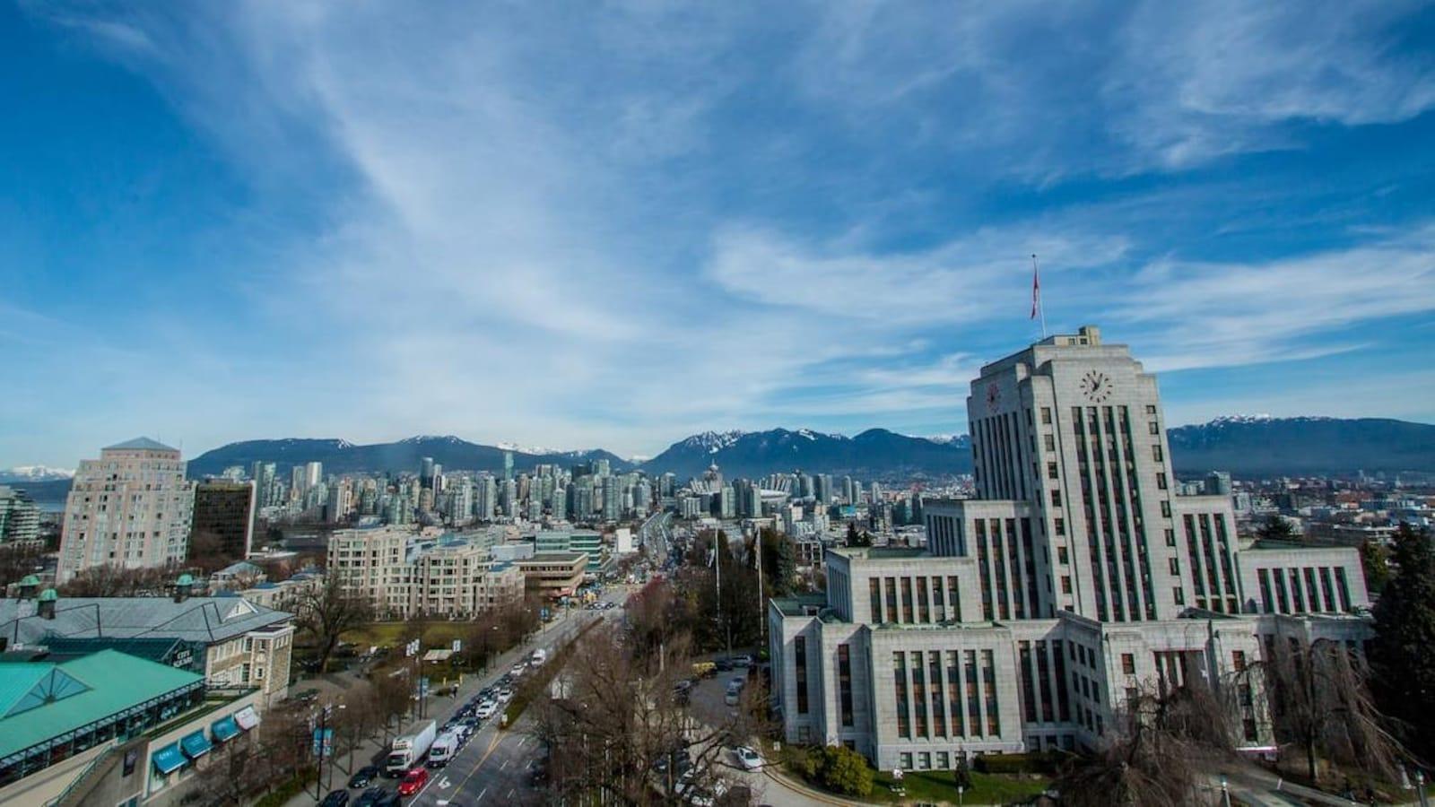 L'hôtel de ville de Vancouver en premier plan, avec le centre-ville derrière et les montagnes de la rive nord en arrière-plan.