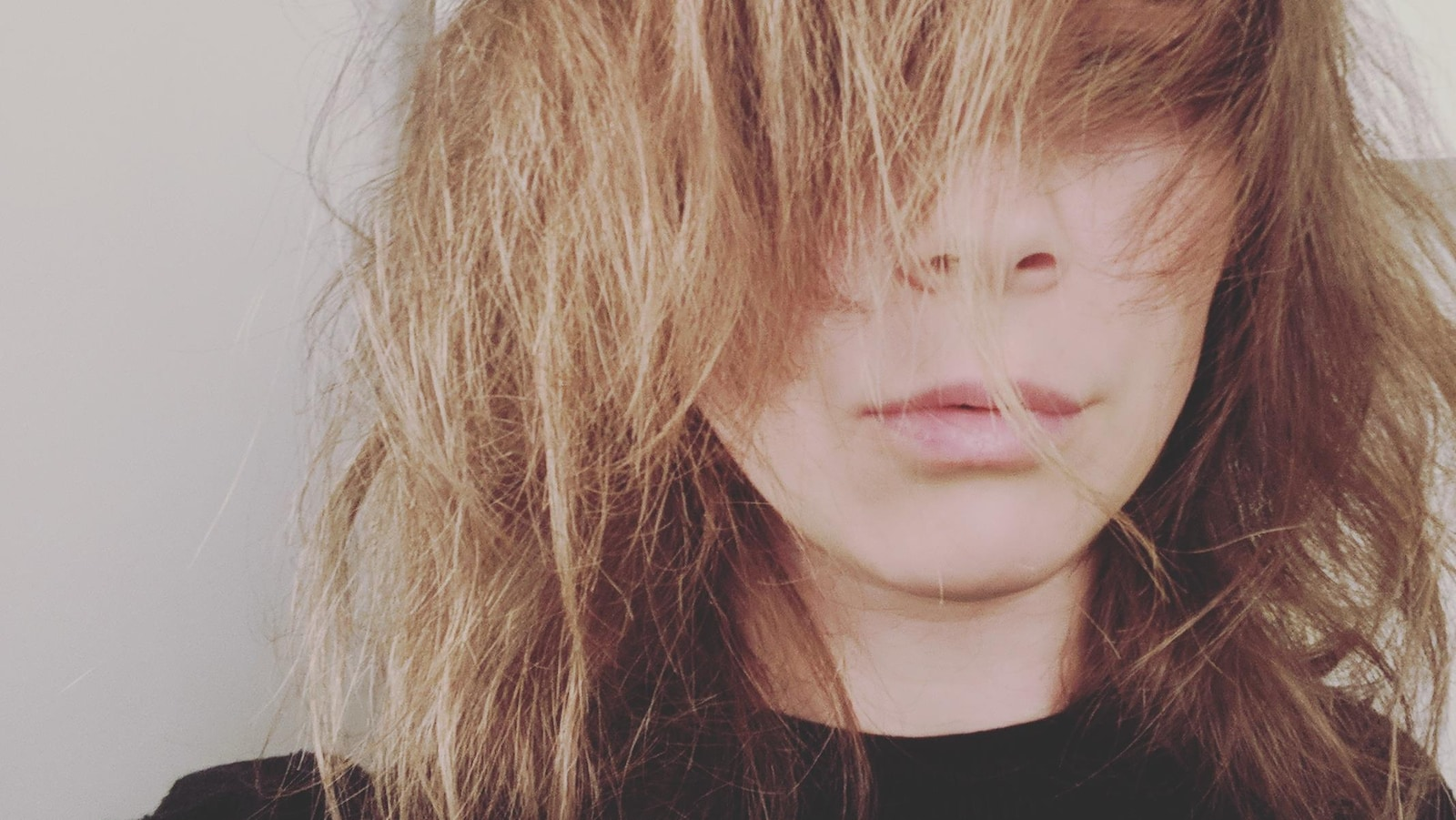 Portrait de Vanessa Bell sur fond gris. Elle porte un chandail noir et ses cheveux blond vénitien cachent son visage.