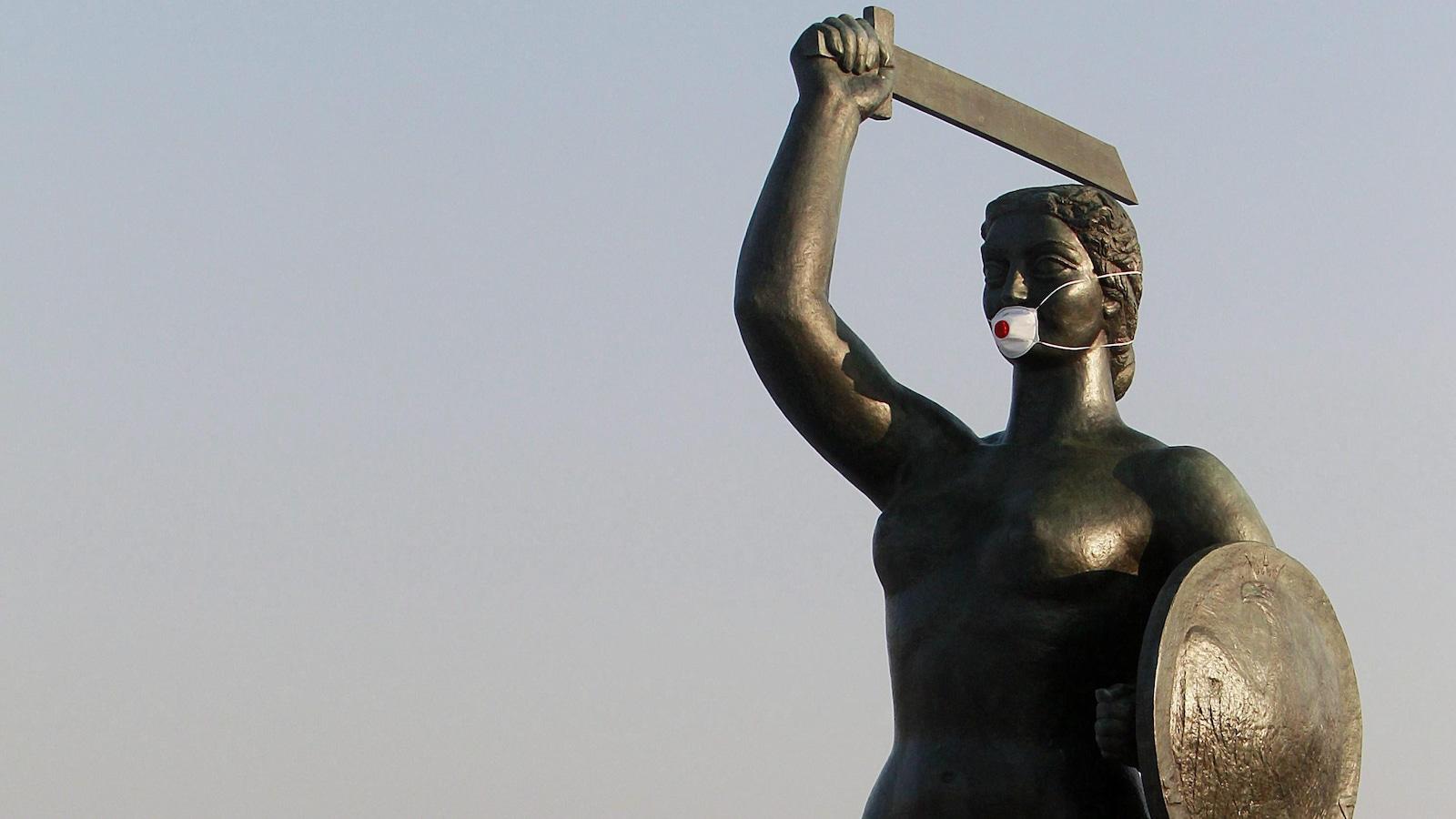 Une statue de sirène avec une épée porte un masque.