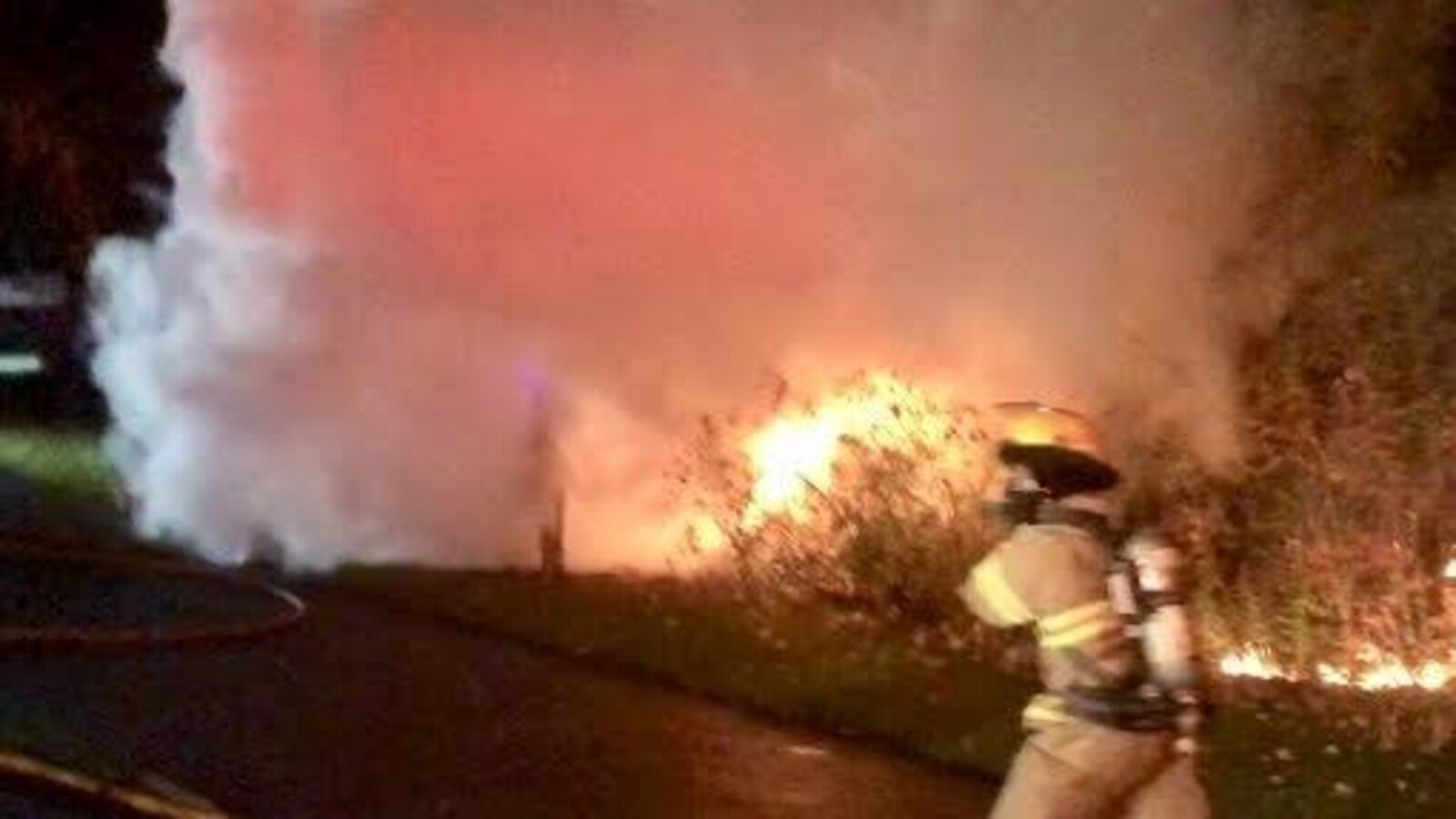 Un pompier se dirigeant vers un véhicule en feu.
